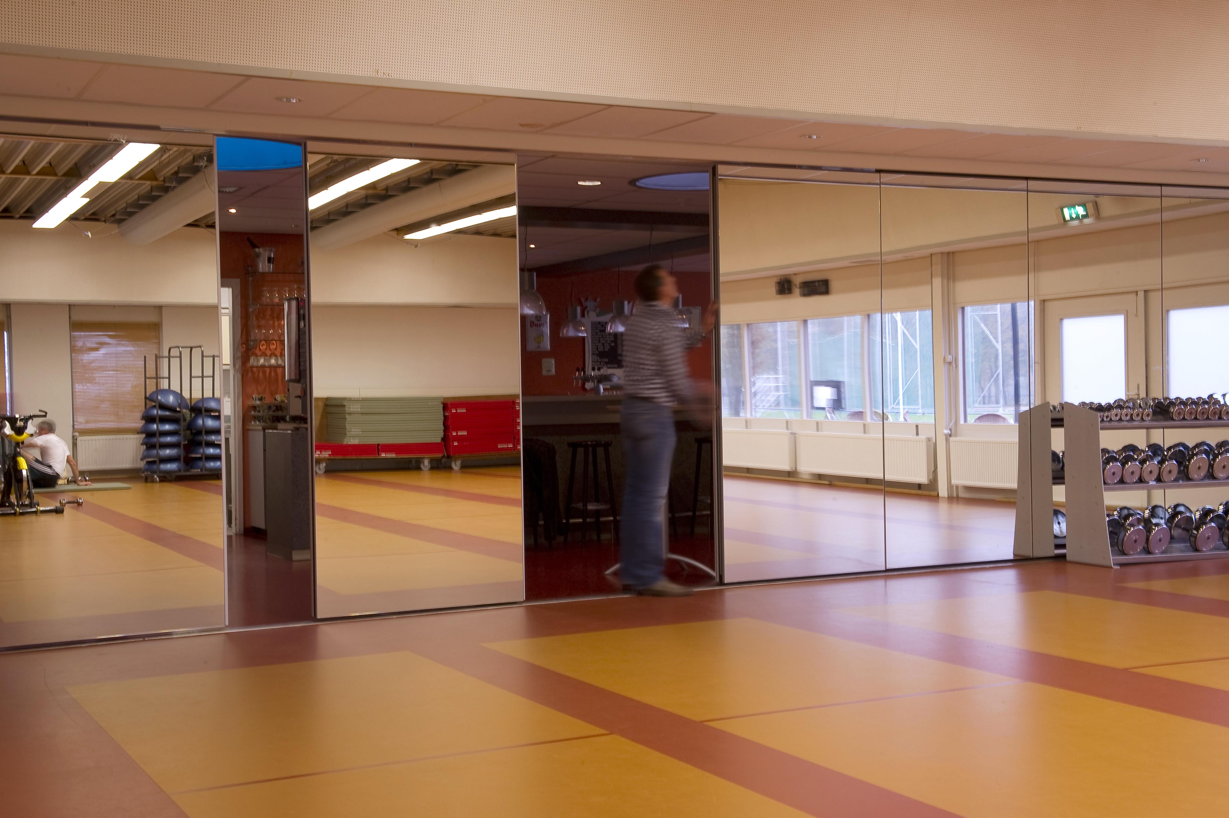 Spiegel op paneelwand in fitnesstuimte